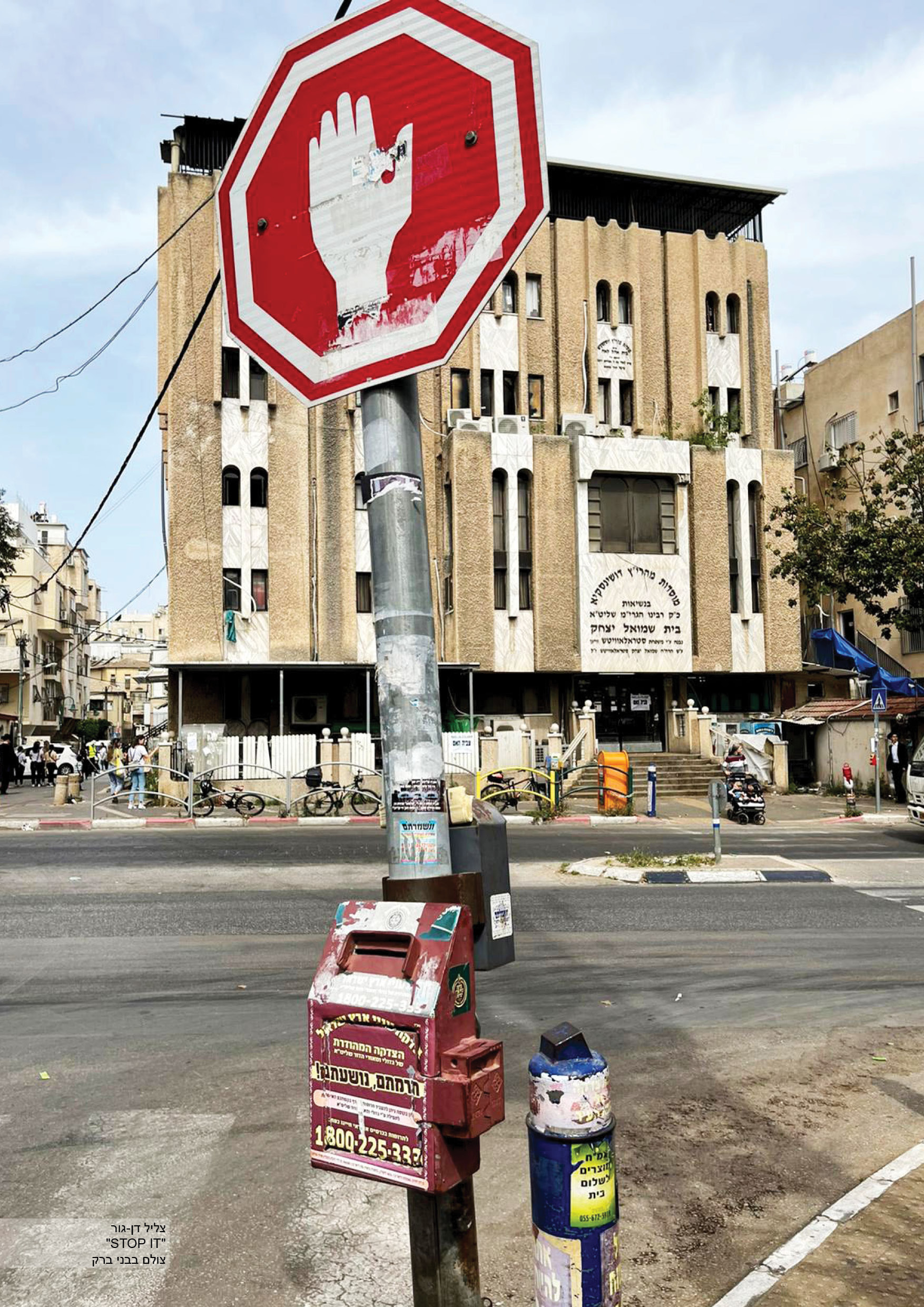 A synagogue at the background with three charity boxes hanged on a signpost in Bnei-Brak. Photo: Tzelil Dan-Gur